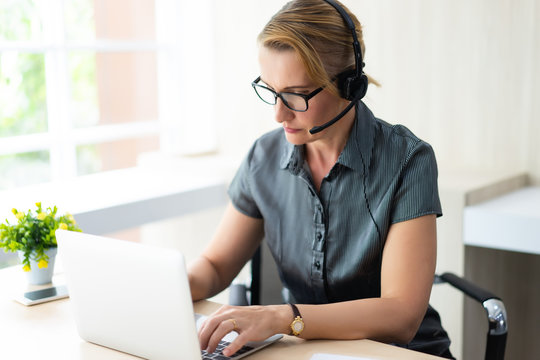 Serious senior woman helpline operator with headphones and using laptop at workplace