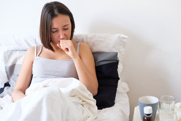 Ill woman coughing and lying in the bed