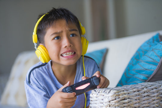 lifestyle portrait of young latin little kid excited and happy playing video game online with headphones holding controller enjoying having fun sitting on couch