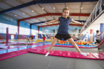 joyful little girl with pigtails and a smile on her face jumping on the trampoline