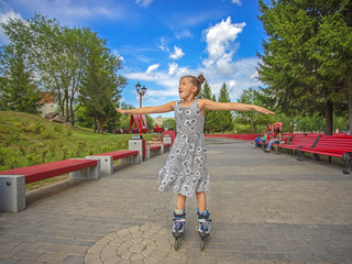 joyful little girl skating on the roller in the city park on a sunny summer day