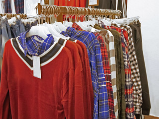 colorful bright hoodies and sweaters hang on hangers in the store