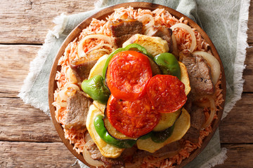 Middle Eastern Dish Maklouba or Makloubeh rice with meat and vegetables close-up on a plate. Horizontal top view