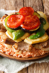 Maklouba or Makloubeh is a very popular Mediterranean and Middle Eastern Dish rice with beef and vegetables close-up. Vertical