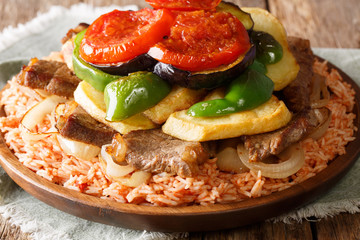 Tasty Lebanese recipe maklouba: rice with beef, eggplant, pepper, onions and tomatoes close-up. horizontal