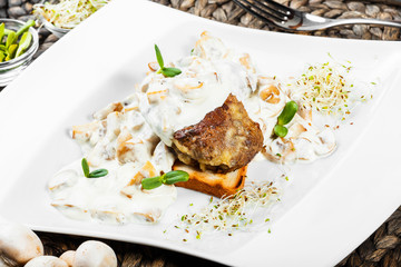 Grilled meat steak veal medallion with cheese sauce with mushrooms on plate. Healthy food. Hot Meat Dishes