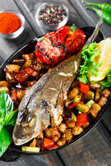 Baked dorado fish with vegetables and lemon on pan on wooden background close up. Delicious dish of seafood