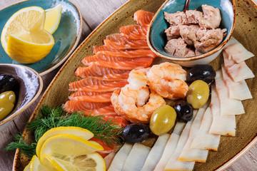Seafood platter. Fresh cod liver, salmon, shrimp, slices fish fillet, decorated with herb, lemon and olives