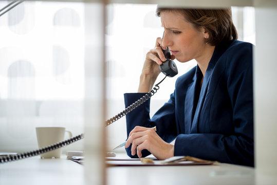Businesswoman or manageress talking on a landline phone