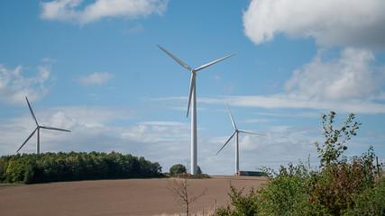 3 Windkrafträder vor blauem Himmel mit Wolken