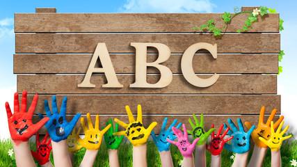"""in bunten Farben angemalte Kinderhände und Schild mit Aufschrift """"ABC"""""""