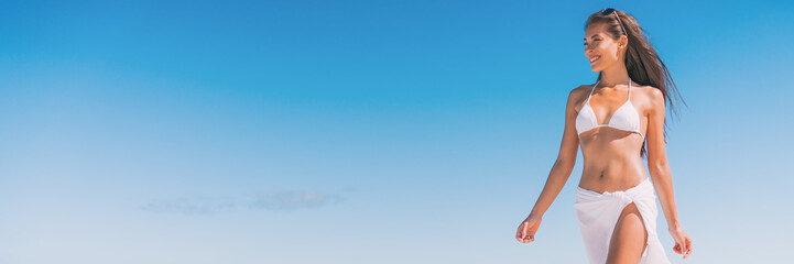 Wall Mural - Luxury beach travel vacation woman relaxing banner walking on blue sky copy space background, lots of copyspace. Asian girl on tropical destination paradise wearing bikini swimwear.