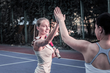 Sport challenge. Beautiful two women exchanging high five and finishing tennis set