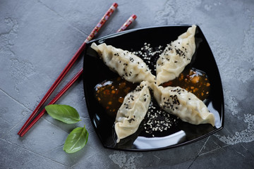 Black plate with steamed korean dumplings, sesame and dipping sauce, high angle view on a grey concrete background, horizontal shot