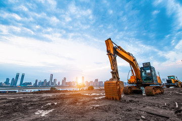 excavator in construction site on sunset sky background Wall mural