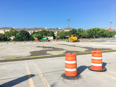 Uncover parking garage lots remodel in progress at wholesale retail store in Lewisville, Texas, US. Row of plastic cones adapters chain barrier and heavy construction equipments, industrial background