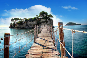 Wall Murals Bridges The wooden bridge overlooking the sea leads to an island with palm trees. It's a rope bridge. It is located in Zakynthos, Greece.