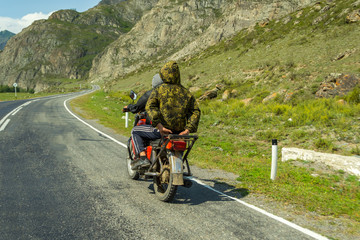 Two guys without helmets ride on an old Soviet red motorcycle on the road in the mountains of the Altai from one village to another, one is dressed in a jacket