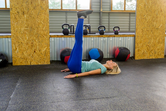 Blonde beatifull woman is making a warm-up lying on the floor raising up legs in the right angle, resting his palms and shoulder blades in the gym on the background of sports equipment