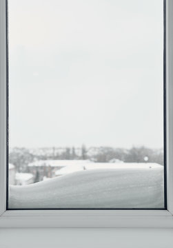 Closeup of winter window view with snowy city landscape