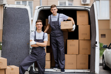 Two young handsome smiling movers wearing uniforms are unloading the van full of boxes. House move, mover service.