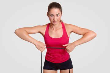 Strong healthy young fitness woman does stretching exercise with fitness gum, dressed in sportswear, looks directly at camera, makes athletic exercises, poses indoor against white background
