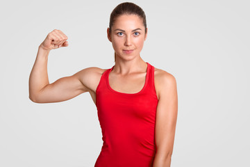 Horizontal shot of self determined young sportswoman in red t shirt, shows her muscles, has training in gym every day, stands against white background. People, wellbeing and lifestyle concept