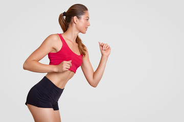 Sideways shot of sporty woman has perfect figure, stands in posture, prepares for jogging, dressed in casual top and shorts, stands against white background with copy space for your text or slogan