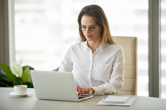 Serious young businesswoman using computer business software applications sitting at office desk, focused employee, boss or secretary working, browsing or communicating online on laptop at workplace