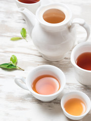 Tea concept,Teapot and cup of herbal tea with green tea leaves on wood