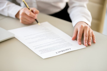 Signing contract concept, businesswoman executive or customer making business deal for insurance, commercial loan bank services, close up view of hand putting written signature on legal document