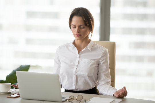 Mindful millennial woman taking break for relaxation meditating in office to reduce work tension, calm successful businesswoman doing yoga exercises feeling zen enjoying no stress free relief concept