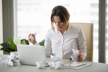 Frustrated stressed businesswoman holding crumpled paper looking at laptop trying to finish urgent work till deadline, disorganized woman writer lost concentration feeling lack of creative ideas