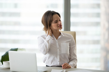 Tired businesswoman feels fatigue massaging tensed muscles of stiff neck trying to relieve pain after sedentary computer work in incorrect posture or uncomfortable office chair, fibromyalgia concept