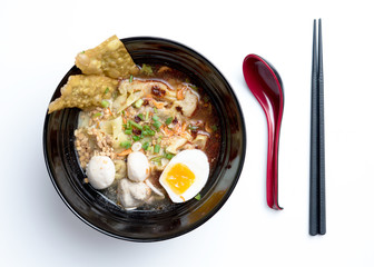Thai spicy noodle,Thai yellow noodle tom yum with pork,egg and meat ball isolated on white