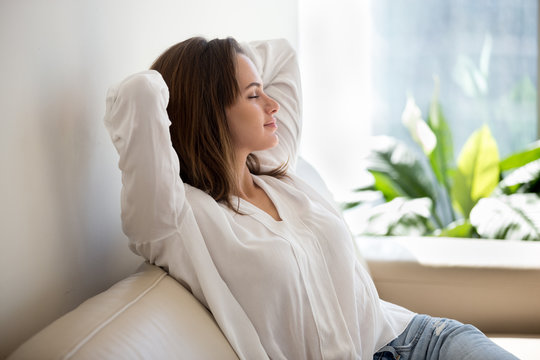 Relaxed calm woman resting breathing fresh air feeling mental balance enjoying wellbeing at home on sofa, satisfied young lady taking pleasure of stress free weekend morning stretching on couch