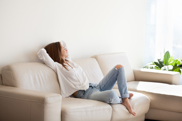 Happy woman relaxing on comfortable soft sofa enjoying stress free weekend at home, calm satisfied girl stretching on couch thinking of pleasant lazy day, dreaming and planning sunday morning Wall mural