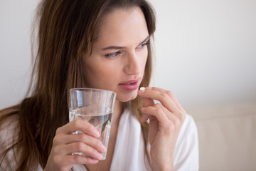 Obraz Doubtful sick ill young woman holding pill and glass of water taking painkiller medicine drugs to relieve headache pain, worried about side effects of antidepressant or emergency contraceptive meds - fototapety do salonu