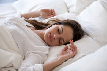 Sleeping woman enjoying healthy nap in cozy bed in the morning, millennial girl relaxing on soft pillow and comfortable mattress with white cotton sheets sleeping well and having enough rest concept
