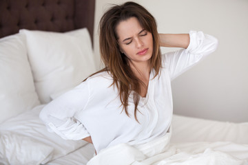 Unhappy young woman waking up in uncomfortable bed feeling ache in back pain massaging tensed muscles of stiff neck after sleep on bad mattress in incorrect posture, fibromyalgia and backache concept