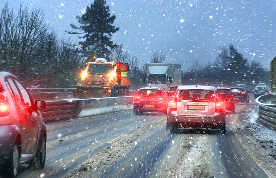 Streufahrzeug bei Schneematsch und Straßenglätte auf Autobahn im Berufsverkehr