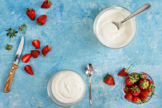 Organic yogurt in a bowl with freshly cut strawberries on a blue coOrganic yogurt in a bowl with freshly cut strawberries on a blue concrete background. Top view and close-up. Flatlay