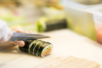 Sushi preparation in japanese restaurant, close up on chief hands cutting roll