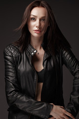 Daring girl model in black leather dress, style of rock, dark make up and beauty hair. Picture taken in the studio.