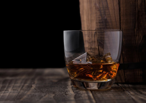 Glass of whiskey with ice cubes next to wooden barrel. Cognac brandy drink