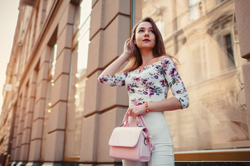 Young woman wearing beautiful outfit and accessories outdoors. Girl holding handbag. Fashion model walking in city Fotomurales