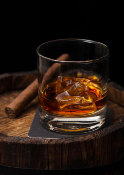 Glass of whiskey with ice cubes and cigar on top of wooden barrel. Cognac brandy drink