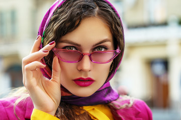 Outdoor close up fashion portrait of young beautiful woman wearing trendy pink, fuchsia color sunglasses, colorful kerchief, posing in street of european city. Copy, empty space for text