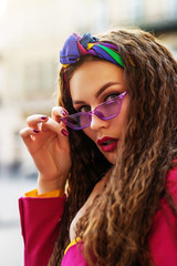 Outdoor close up fashion portrait of young beautiful woman wearing trendy violet sunglasses, colorful headband, posing in street of european city