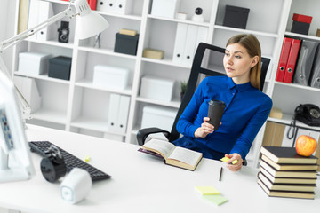 A young girl sits at a computer desk and holds a glass with coffee and a yellow marker in her hand. Before the girl lies an open book.